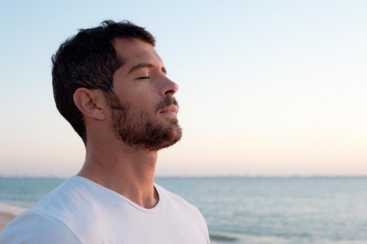 Hombre en la playa meditando